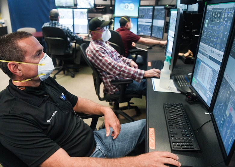 Daryl Osteen, left, a test operations engineer, John VanScoten, an outside machinist, and other Team AEDC personnel work in the control room of the Arnold Engineering Development Complex (AEDC) Aerodynamic and Propulsion Test Unit (APTU), May 20, 2020, while wearing masks to help mitigate risk associated with the coronavirus pandemic. The APTU team has performed their tasks, providing hypersonic testing capabilities, without interruption during the pandemic. Hypersonics is considered a critical field for national defense. (U.S. Air Force photo by Jill Pickett)