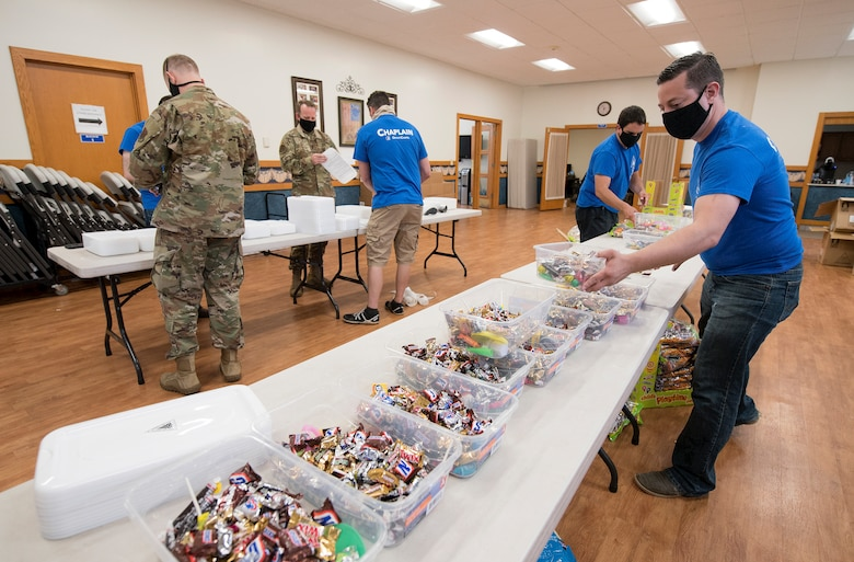service members fill containers with candy, knickknacks and toys