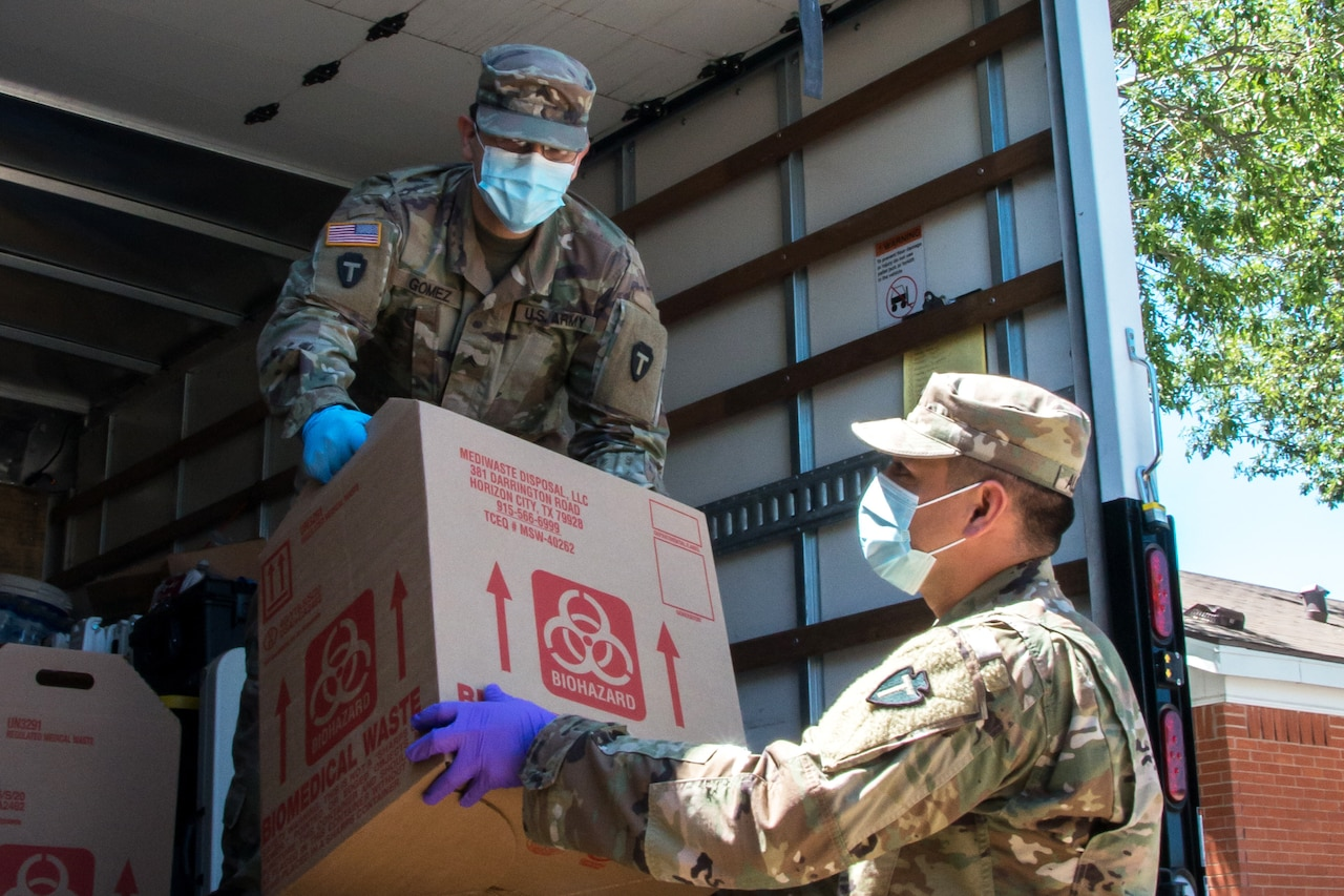 Service members wearing masks and gloves unload a box from a large truck.