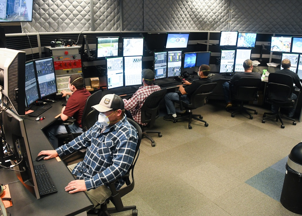Personnel work in the control room of the Arnold Engineering Development Complex (AEDC) Aerodynamic and Propulsion Test Unit (APTU), May 20, 2020, while wearing masks to help mitigate risk to COVID-19