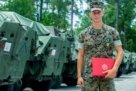 U.S. Marine Corps Cpl. Matthew T. Ubl, a light armored vehicle repair technician with Alpha Company (Co.), 2d Light Armored Reconnaissance Battalion (LAR), 2d Marine Division (MARDIV), salutes Lt. Col. Christopher Conner, the commanding officer for Alpha Co., 2d LAR, on Camp Lejeune, North Carolina, June 4, 2020. Ubl received a Navy and Marine Corps Commendation Medal for his efforts executing cardiopulmonary resuscitation (CPR) for 15 minutes on an unknown, unconscious civilian, which contributed to saving the man's life. (U.S. Marine Corps photo by Sgt. Stormy Mendez)
