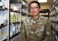 Spc. Jihoon Jeong, a combat medic with 4th Battalion, 31st Infantry Regiment, 2nd Brigade Combat Team, 10th Mountain Division (LI), and a native of Mount Holly, N.J., stands in front of medication storage at the Guthrie Ambulatory Healthcare Clinic Pharmacy in Fort Drum, N.Y. June 3. Jeong holds a doctor of pharmacy degree and is currently credentialed to work as a pharmacist in the clinic during the COVID-19 crisis. He's using his experience in the pharmacy to prepare him to commission as a pharmacy officer in the Army.