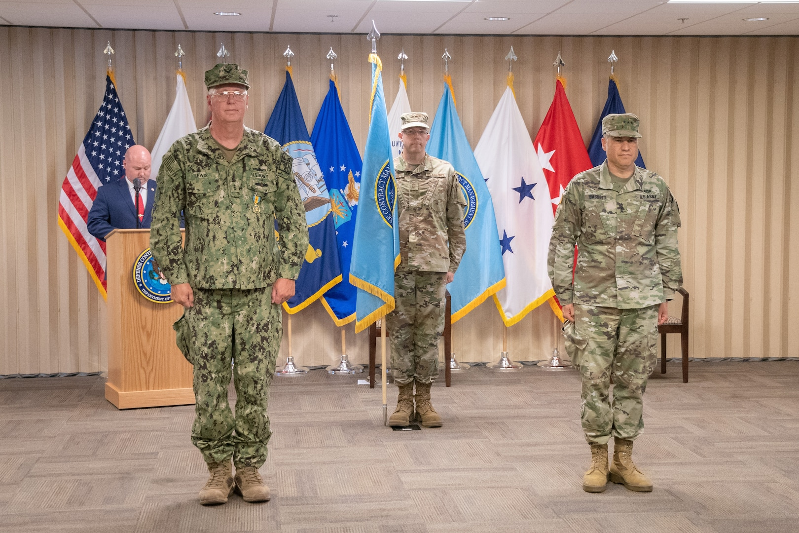 Three men in uniform stand in a formal manner