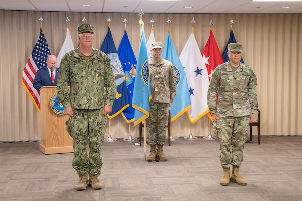 Three men in uniform stand in a formal manner
