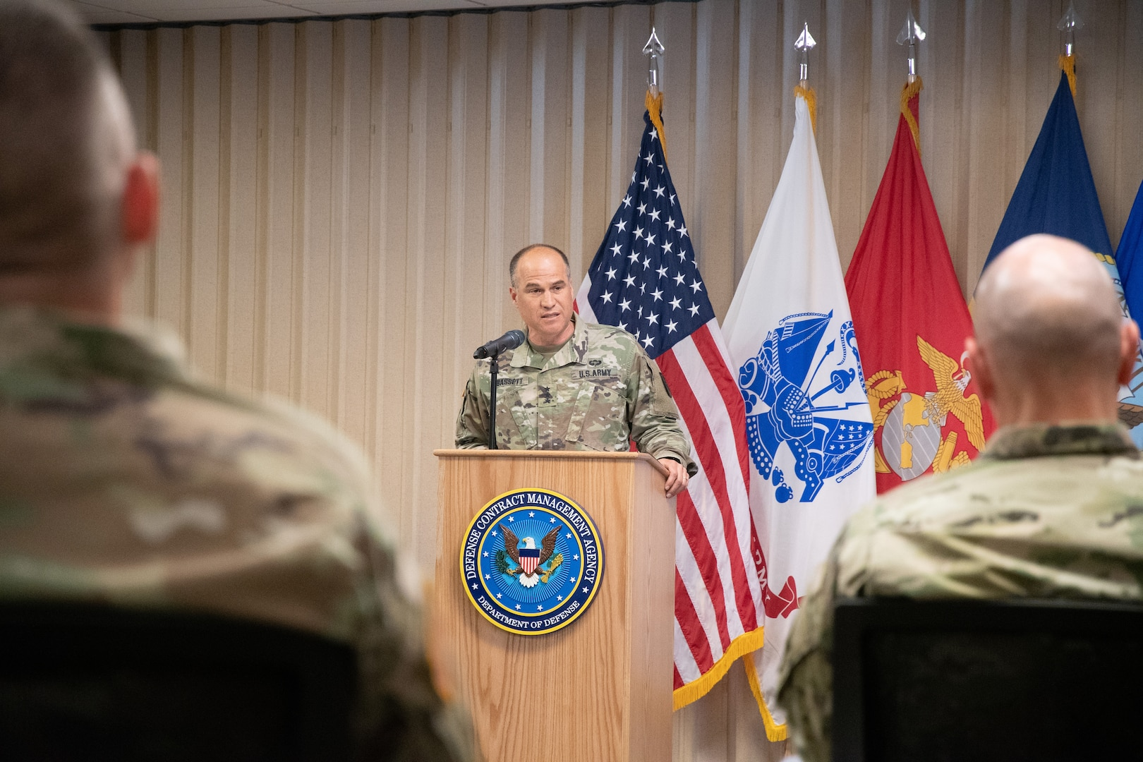 An Army general speaks from a podium in front of flags