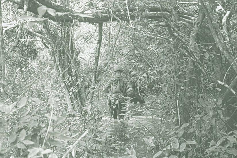 Two men in battle uniforms walk through a swamp in a dense jungle.