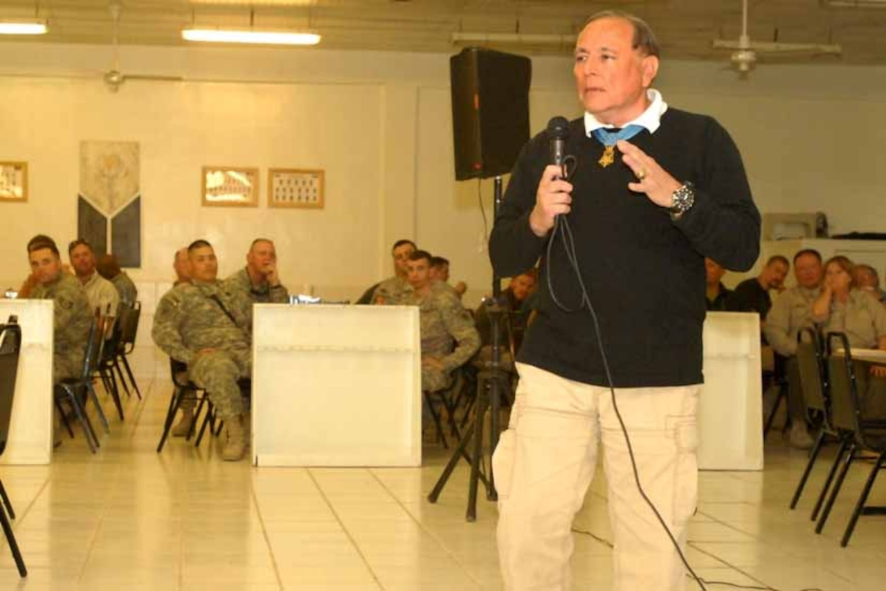 An older man with a microphone talks to several seated soldiers.