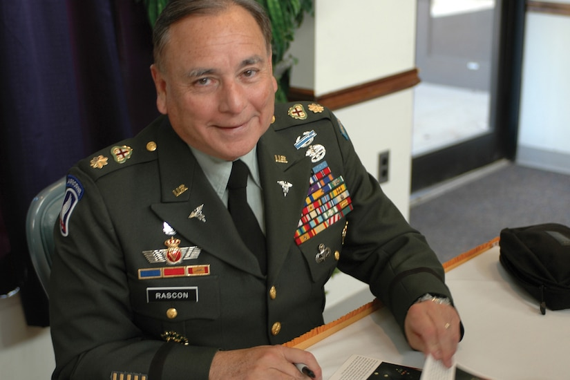 A man in a military uniform sits at a table autographing photos.