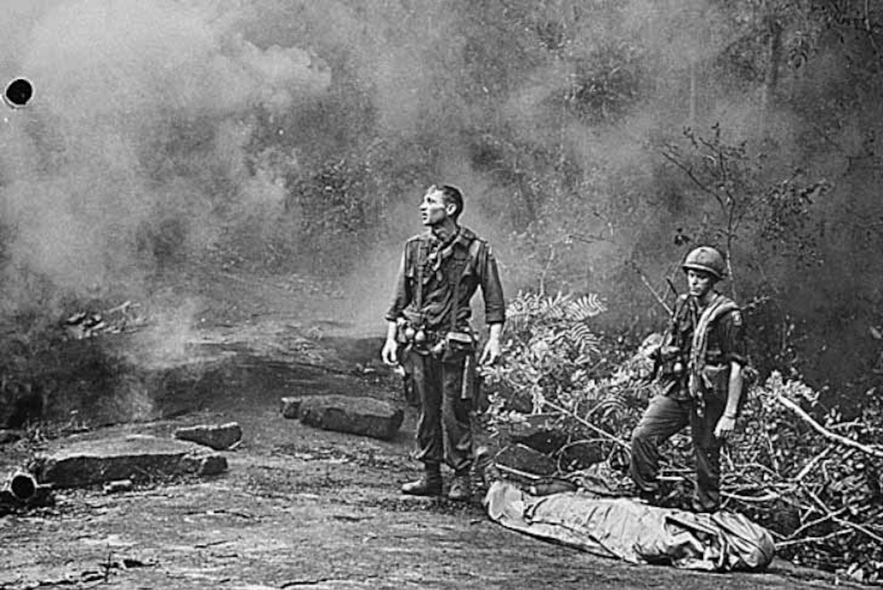 Two soldiers stand beside a body bag in the jungle.