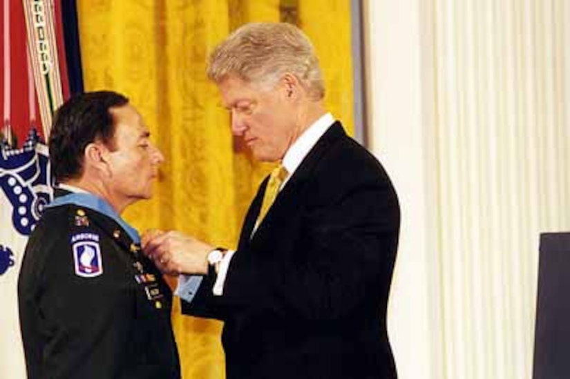 A man adjusts a medal around another man's neck.