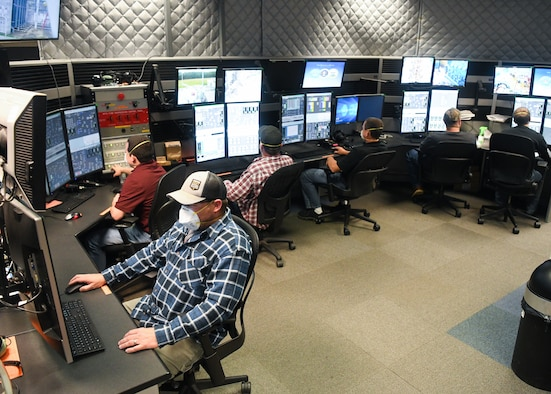 Joseph Cowan, left, an outside machinist, and other Team AEDC personnel work in the control room of the Arnold Engineering Development Complex (AEDC) Aerodynamic and Propulsion Test Unit (APTU), May 20, 2020, while wearing masks to help mitigate risk associated with the coronavirus pandemic. The APTU team has performed their tasks, providing hypersonic testing capabilities, without interruption during the pandemic. Hypersonics is considered a critical field for national defense. (U.S. Air Force photo by Jill Pickett)