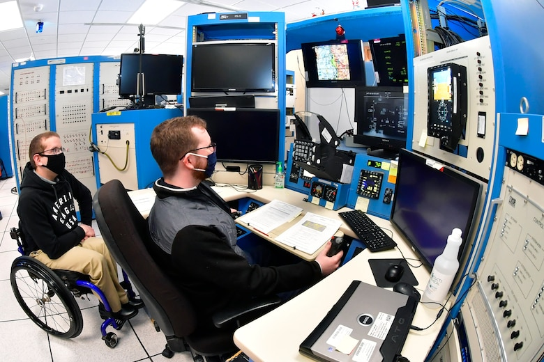 Austin Eberle and Collin Lindeman, both System Test engineers, 518 Software Engineering Squadron, preform software test and evaluation on an F-16 simulator, May 26, 2020, at Hill Air Force Base, Utah. (U.S Air Force photo by Todd Cromar)