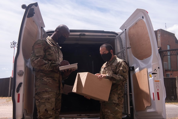 Staff Sgt. Isaac Darko and Staff Sgt. Isaac Portocarrero, Defense Courier Station Mildenhall defense couriers, load packages into a mission vehicle at RAF Mildenhall, England, June 2, 2020. Factors such as the size of the asset and delivery destination dictate the mode of transportation defense couriers use to move items. (U.S. Air Force photo by Airman 1st Class Joseph Barron)