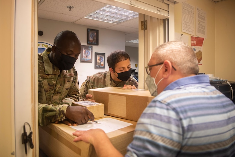 Staff Sgt. Isaac Darko, left, Defense Courier Station Mildenhall defense courier, and Tech. Sgt. Raul Pedroza, right, DCS Mildenhall noncommissioned officer in charge, review asset information with a customer at RAF Mildenhall, England, June 2, 2020. Defense couriers oversee the processing, storage and transportation of sensitive materials. (U.S. Air Force photo by Airman 1st Class Joseph Barron)