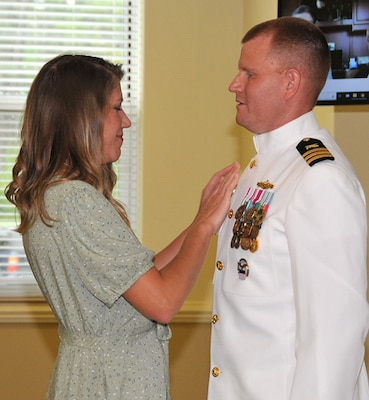 Brittanie May places command pin on Navy Cmdr. Isaac May's uniform