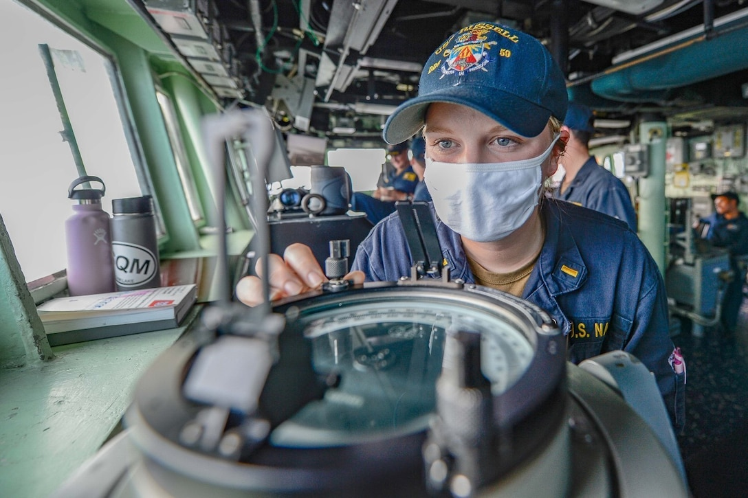 A sailor looks through a pelorus in the pilot house of a military ship.