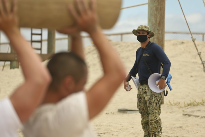A  Navy SEAL looks at sailors carry a log over their heads.