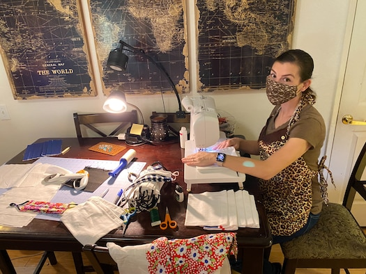 A woman sits at her sewing machine sewing masks equipped with windows so people can read the lips of the mask wearer.