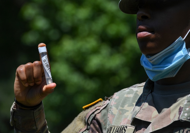 A U.S. Army Soldier holds up a mass rapid COVID-19 test sample during testing at Joint Base Langley-Eustis, Virginia, June 3, 2020. The pilot test for the oral swabs will help the Department of Defense evaluate the alternate method's effectiveness, impact and mass testing capabilities. (U.S. Air Force photo by Senior Airman Monica Roybal)