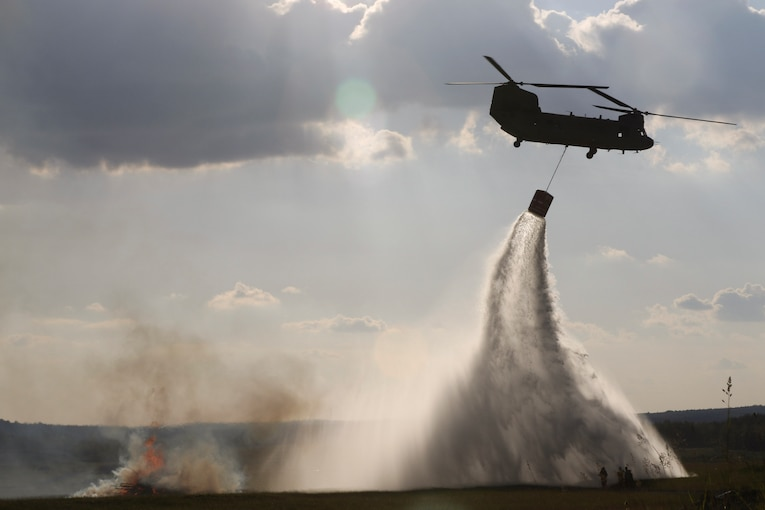 An Army helicopter holds a bucket dropping water by rope.