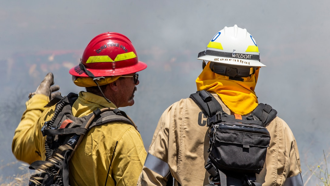 A firefighter with the Camp Pendleton Fire Department explains the scheme of maneuver to another firefighter during a controlled burn training exercise on Marine Corps Base Camp Pendleton, Calif., June 3.