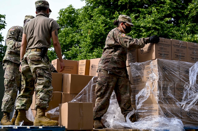 National Guardsmen in protective gear pick up boxes.