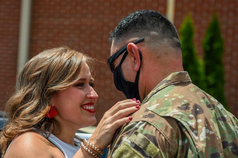 An airman hugs his spouse.