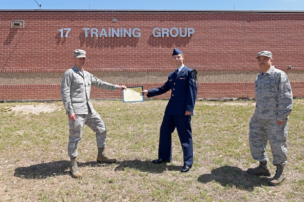 U.S. Air Force Col. Thomas Coakley, 17th Training Group commander, presents the 316th Training Squadron Student of the Month award to Airman 1st Class Jonathan Zamora, 316th TRS student, at Brandenburg Hall on Goodfellow Air Force Base, Texas, June 5, 2020. The 316th TRS' mission is to conduct U.S. Air Force, U.S. Army, U.S. Marine Corps, U.S. Navy and U.S. Coast Guard cryptologic, human intelligence and military training. (U.S. Air Force photo by Senior Airman Zachary Chapman)