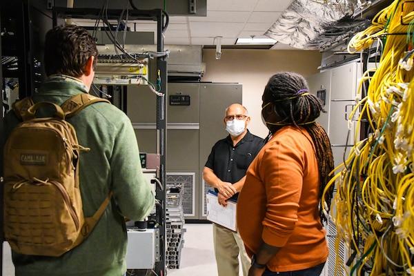 three men talk in a server room
