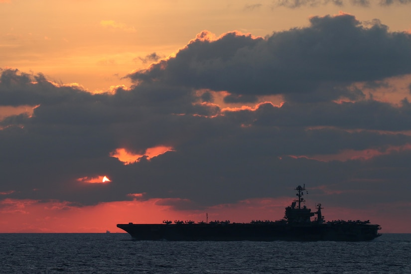 A photo shows the silhouette of an aircraft carrier at sunset.