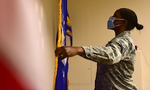 Staff Sgt. Tiffany pulls out the Air Force flag behind the United States flag.