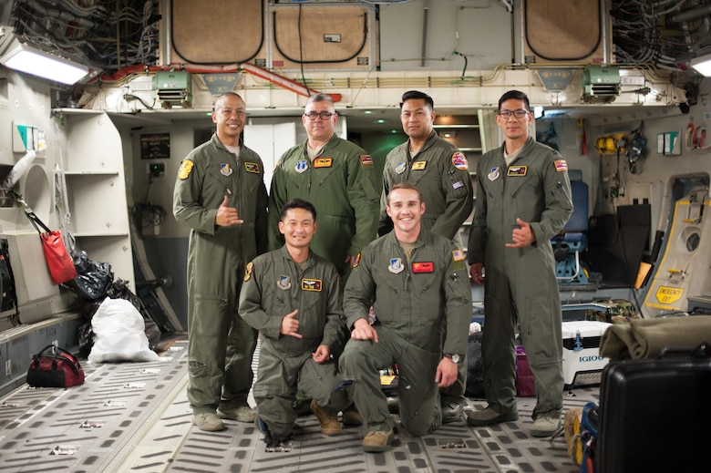 204th Airlift Squadron Airmen, Master Sgt. Brandon Sarceda, Senior Master Sgt. Kale Barney, Maj. Kalei Ho'opai, Capt. Justin Sato, Tech. Sgt. Sean Chang, and a member of the 535th AS, 1st Lt. Andrew Lightsinn, celebrate their arrival at Joint Base Pearl Harbor-Hickam, Hawaii, March 31, after completing a 41-hour aeromedical-evacuation mission.