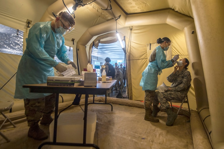 Soldiers in protective medical gear work inside a tent-like structure.