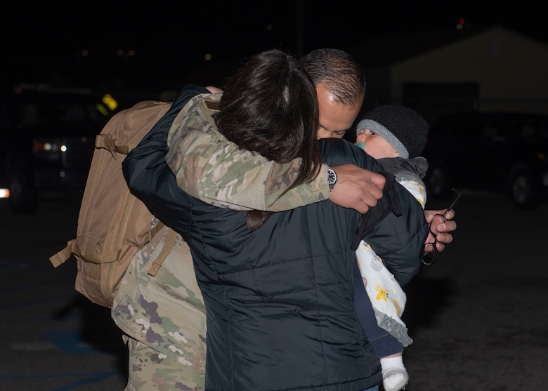 U.S. Air Force Maj. Jesus Burciaga, 726th Air Control Squadron director of operations, hugs his family, May 21, 2020, at Mountain Home Air Force Base, Idaho. The 726th Air Control Squadron returned from an eight month long deployment that was extended due to the COVID-19 pandemic. (U.S. Air Force photo by Airman 1st Class Natalie Rubenak)