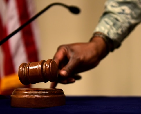 Airman sets down a gavel on a table.
