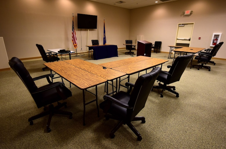 Tables, chairs, and flags are set up in a room to look like a court room.