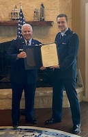 Retired Air Force Maj. Glenn Taylor, left, and son Jordan, display Jordan's commissioning certificate into the United States Air Force May 22, 2020. The event marked the third child the elder Taylor, lead cyber analyst for OSI 3rd Field Investigations Squadron, Joint Base San Antonio-Lackland, Texas, has commissioned into the USAF. (Photo courtesy 3 FIS)