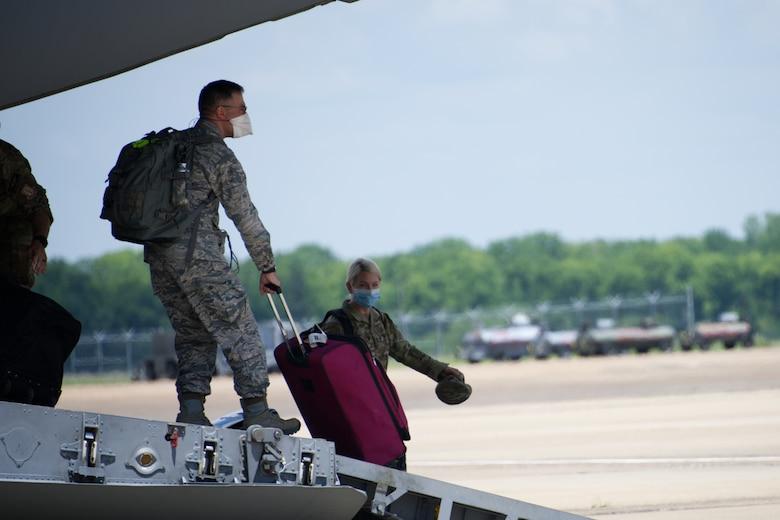 Airmen depart a C-17 Globemaster