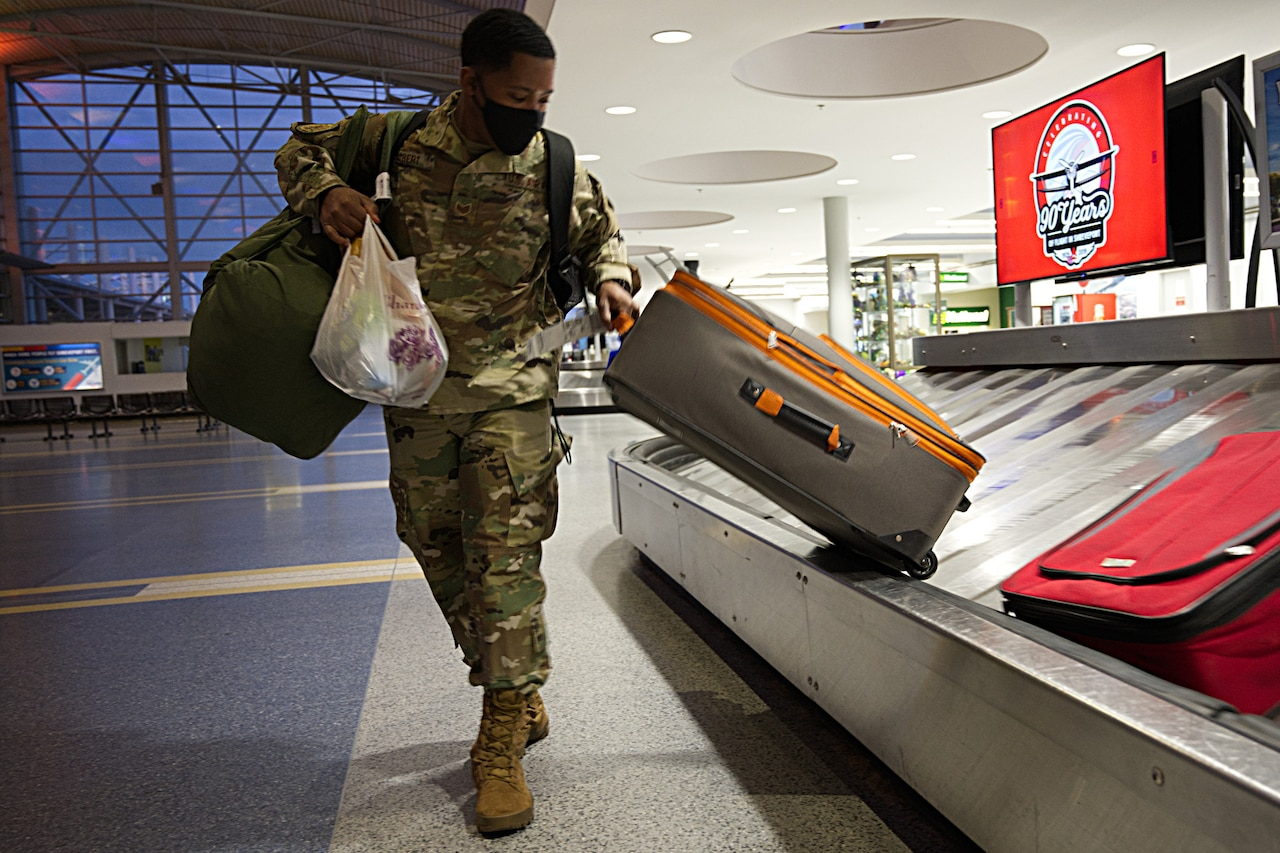 Airman takes luggage from carousel at airport.
