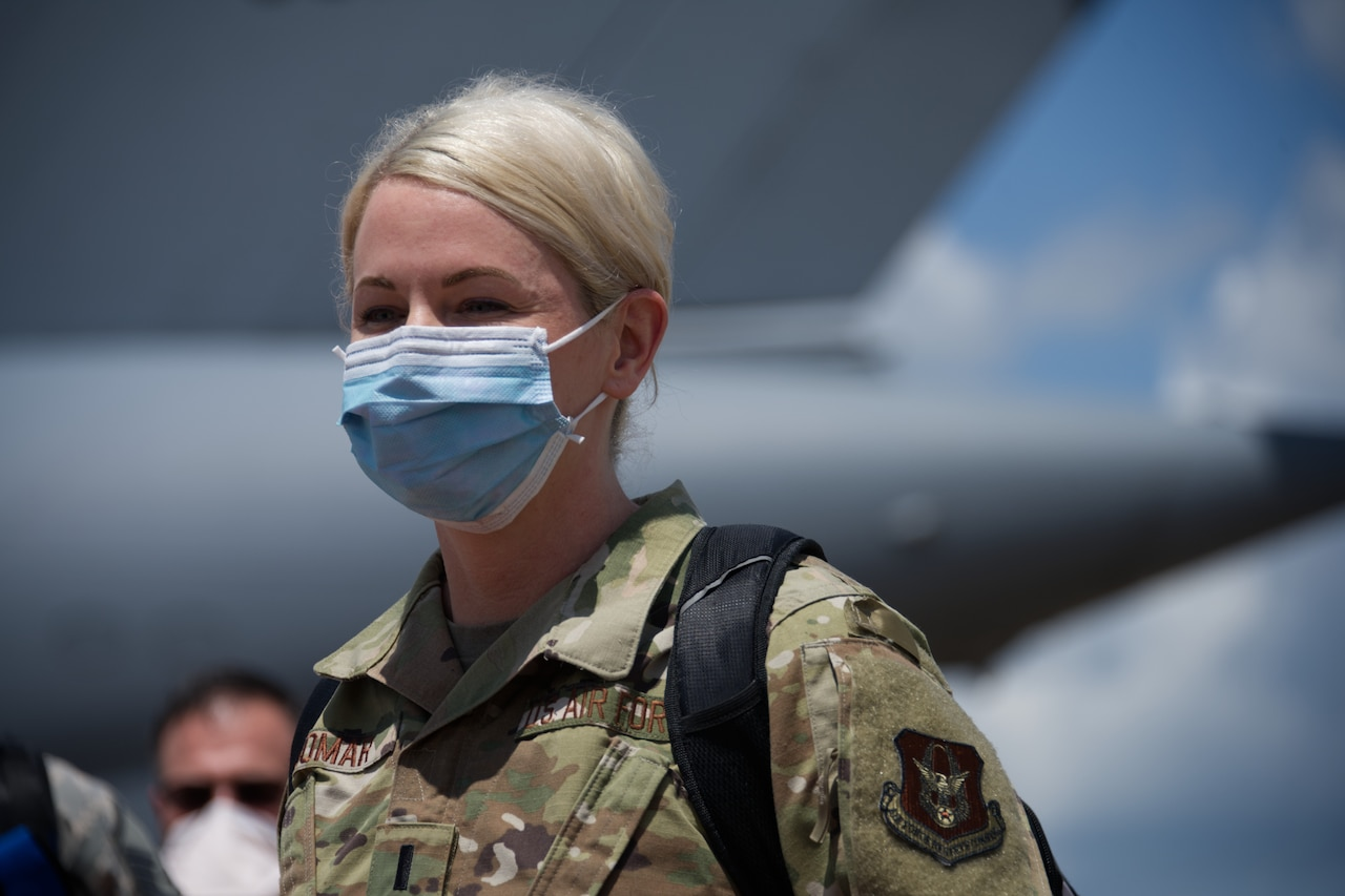 Airman stares across flight line while wearing mask.