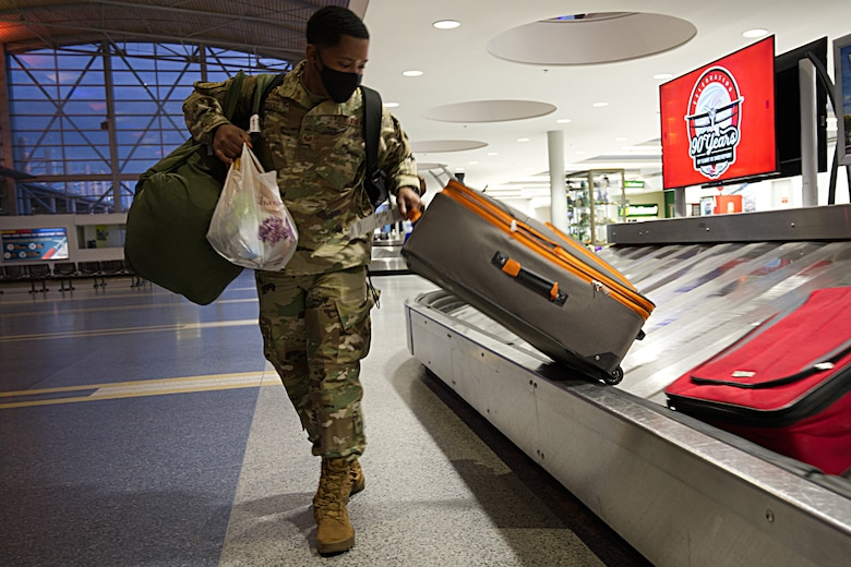 Staff Sgt. Trevor Talbert, an aerospace medical technician, grabs his luggage after arriving in Shreveport, Louisiana, in May. RAPTR is a new tool to help Reservists decide whether it is safe to travel during the pandemic. (Master Sgt. Ted Daigle)