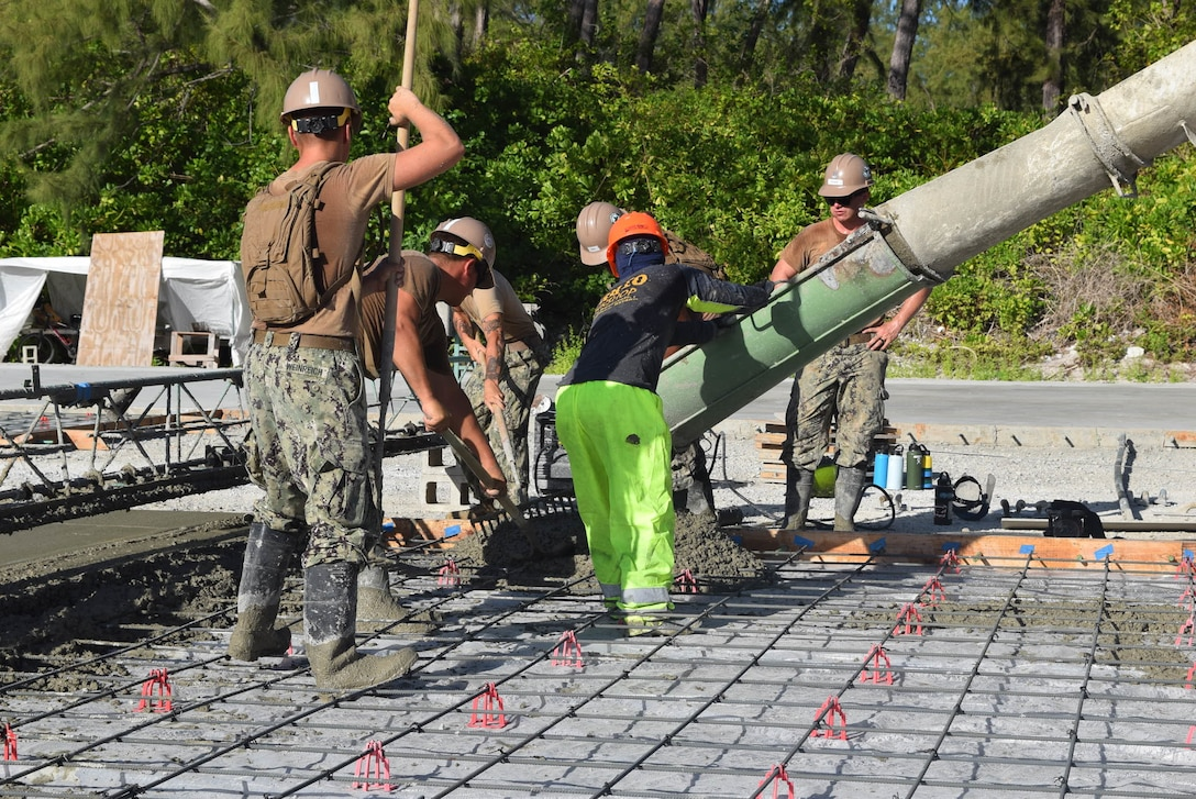 British Indian Ocean Territory (Dec. 11, 2019) U.S. Navy Seabees deployed with Naval Mobile Construction Battalion (NMCB) 5's Detail Diego Garcia work with civilian contractors during a concrete placement that will form a pad for the foundation for a tension fabric structure in support of the U.S. Air Force. NMCB-5 is deployed across the Indo-Pacific region conducting high quality construction to support U.S. and partner nations to strengthen partnerships, deter aggression, and enable expeditionary logistics and naval power projection.