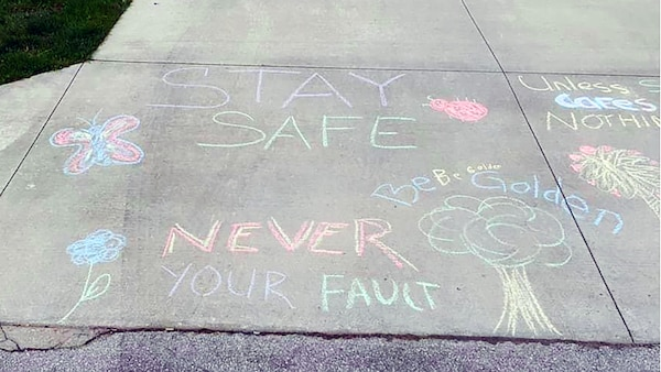 "Messages of support for sexual assault survivors written in chalk include ""stay safe,"" and ""never your fault."""