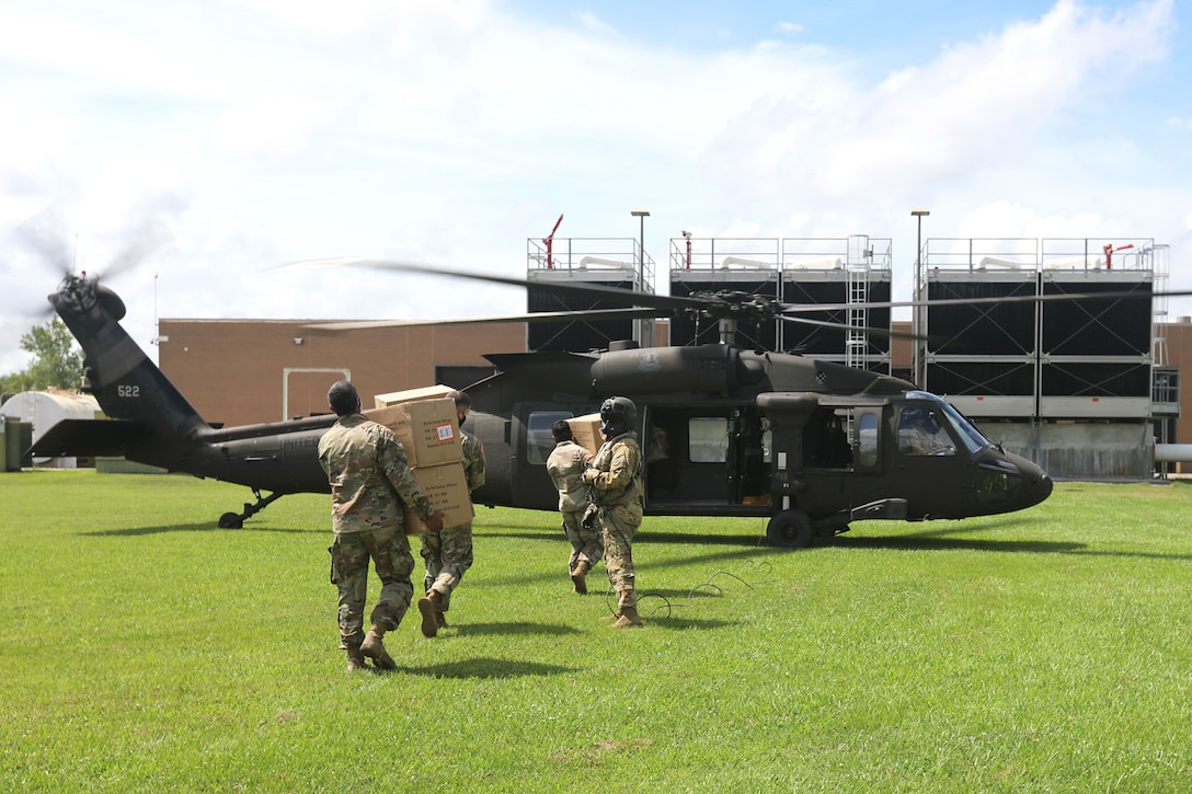 Soldiers carry boxes of supplies to a military helicopter.