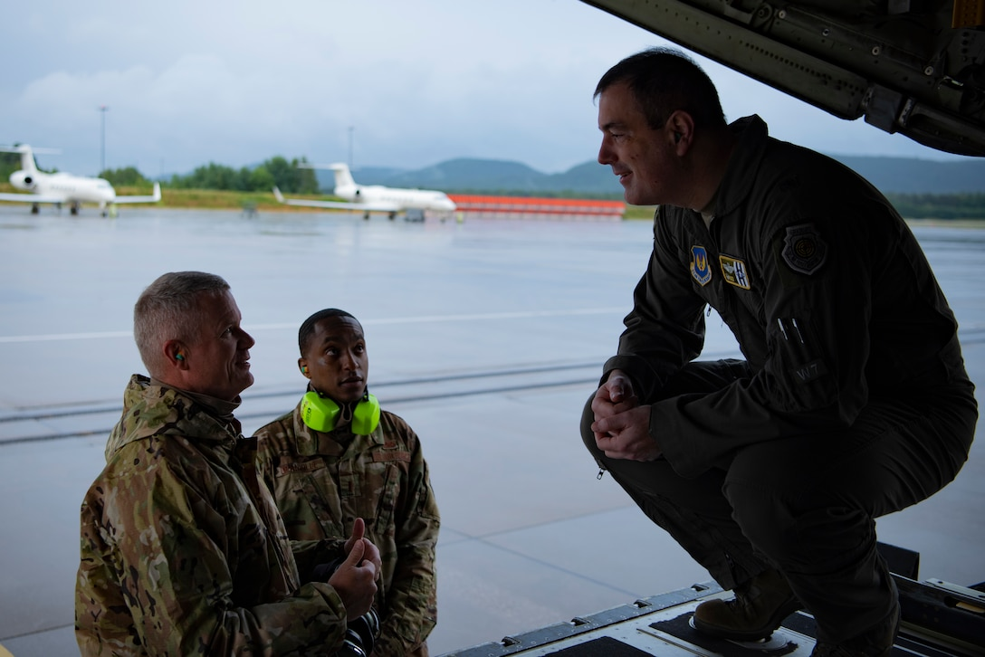 A photo of an Airmen talking to other Airmen
