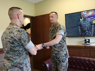 U.S. Marine Corps Sgt.Maj. Christopher Adams (center), the outgoing Sergeant Major of U.S. Marine Corps Security Force Regiment (MCSFR), Fleet Marine Force Atlantic, U.S. Marine Corps Forces Command, hands a noncommissioned officer sword to Col. Corey M. Collier (left), the commanding officer of MCSFR, during a relief and appointment ceremony June 3, 2020 at Naval Weapons Station Yorktown, Virginia. The ceremony was conducted virtually, as part of MCSFR's COVID-19 response measures, and signifies the passing of responsibilities from Sgt.Maj. Christopher Adams to Sgt.Maj. Christopher J. Easter as the Regimental Sergeant Major for MCSFR. (U.S. Marine Corps photo by Staff Sgt. Jessika Braden/ Released)