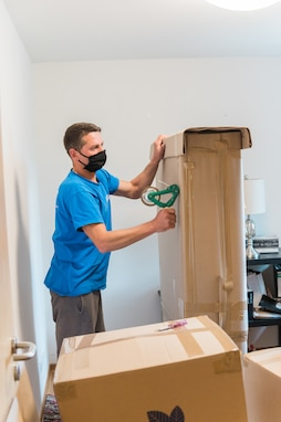 WIESBADEN, Germany - A mover tapes up a box at an apartment at U.S. Army Garrison Wiesbaden May 22 while following health protocols. The Department of Defense has directed that moving personnel adhere to Centers for Disease Control and Prevention protocols regarding health protection, such as wearing face coverings and washing hands, while working in a person's home. (U.S. Army photo by Lisa Bishop)