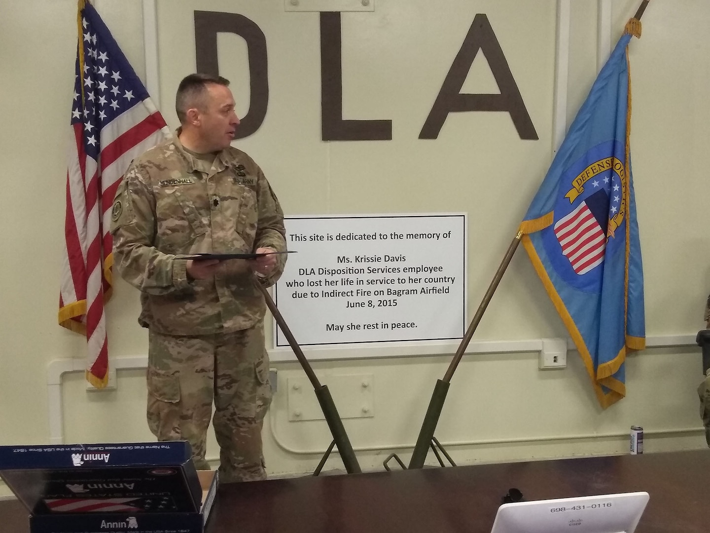 Army Lt. Col. Ryan Mendenhall, officer-in-charge for DLA Disposition Services in Afghanistan, addresses his team as they assemble by the memorial display to remember fallen employee Krissie Davis and her sacrifice.