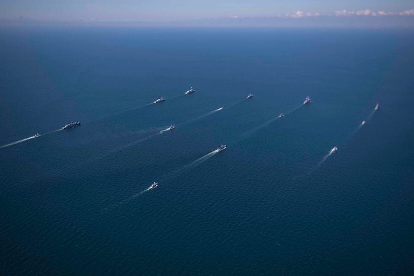 Ships of many nations steam in formation.