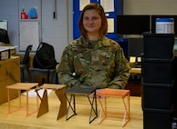 An Airman stands behind four prototypes of a curing rack the used for Nasopharyngeal swabs.